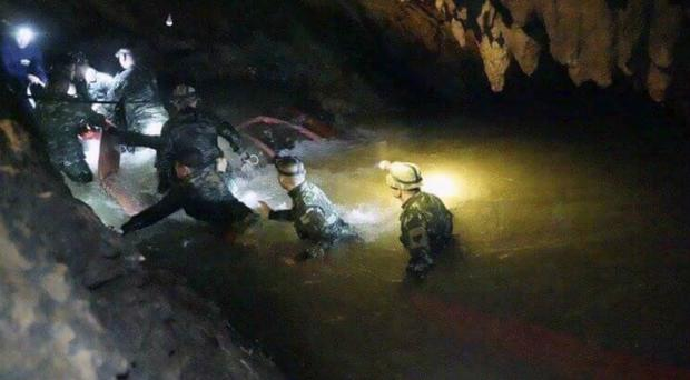 Thai rescue teams walk inside cave complex ((Tham Luang Rescue Operation Centre via AP))
