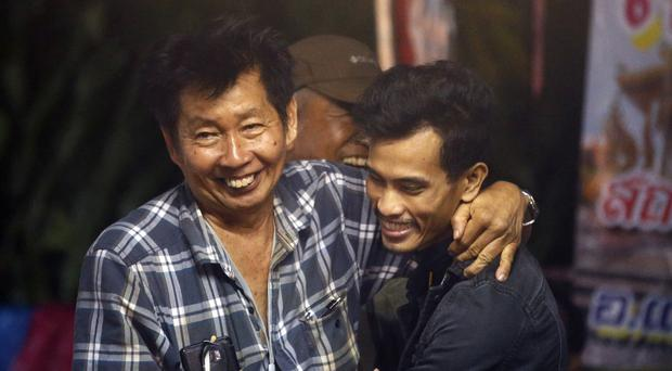 Family members smile after hearing the news that the missing 12 boys and their soccer coach have been found (Sakchai Lalit/PA)