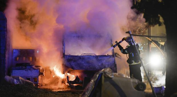 A firefighter works to extinguish a burning vehicle in Nantes (Franck Dubray/AP)