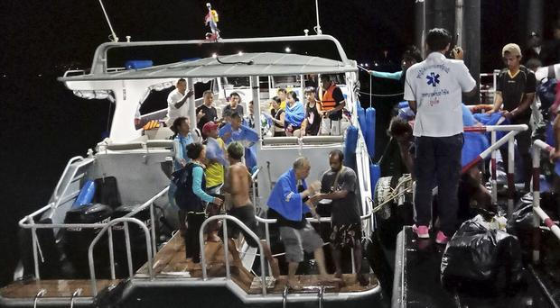 Rescued tourists from a boat that sank are helped on to a pier on the island of Phuket (Thailand Royal Police via AP)