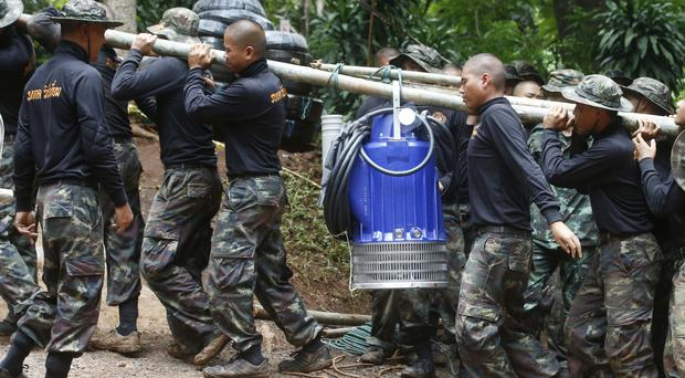 Soldiers carry a pump to help drain the rising flood water in a cave where 12 boys and their football coach have been trapped since June 23 (Sakchai Lalit/AP)