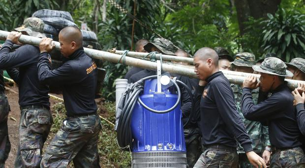Soldiers carry a pump to help drain the rising flood water in a cave (Sakchai Lalit/AP)