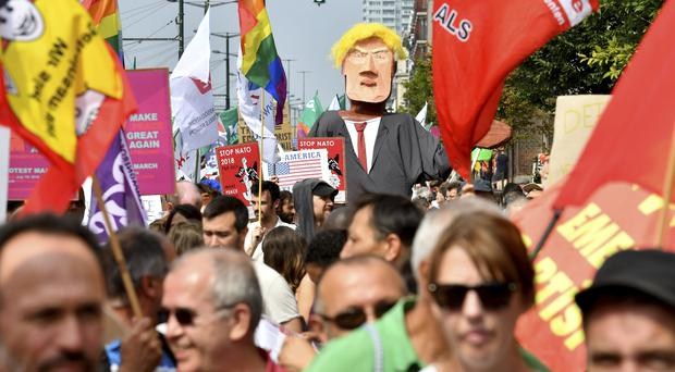 Protesters march next to a giant puppet of Donald Trump (Geert Vanden Wijngaert/AP)