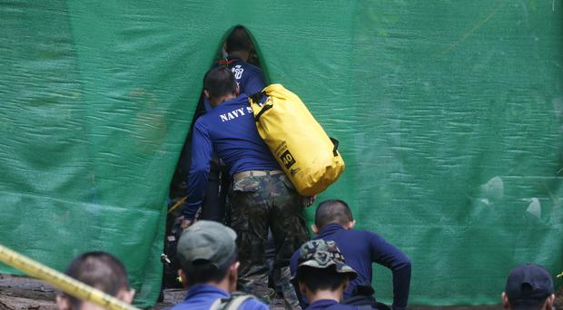 Rescuers arrive near the cave where 12 boys and their football coach have been trapped (Sakchai Lalit/AP)