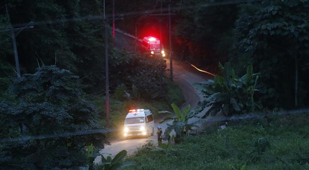 Two ambulances with flashing lights leave the cave rescue area in Thailand (Sakchai Lalit/AP)