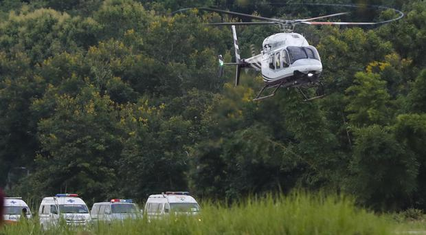 A helicopter believed to be carrying one of the rescued boys lands in Chiang Rai in Thailand (Vincent Thian/AP)