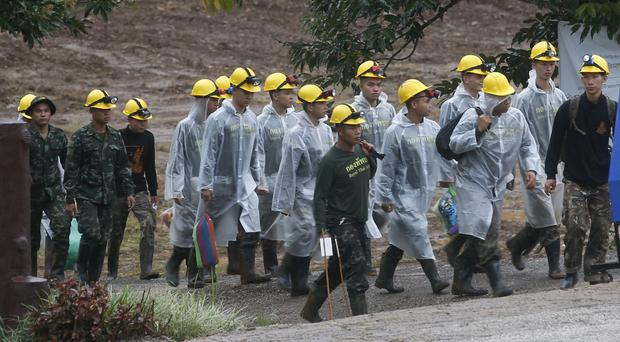 Rescuers walk towards the entrance of the cave complex in Thailand (Sakchai Lalit/AP)