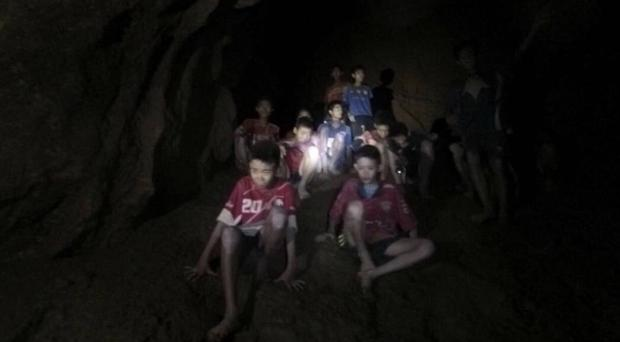 The boys and their coach as they were found in a partially flooded cave Thailand (Tham Luang Rescue Operation Centre/AP)