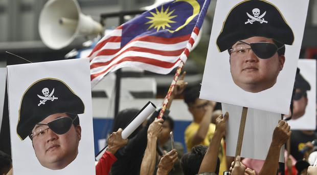 Demonstrators hold portraits of Jho Low illustrated as a pirate during a protest in Kuala Lumpur (AP)