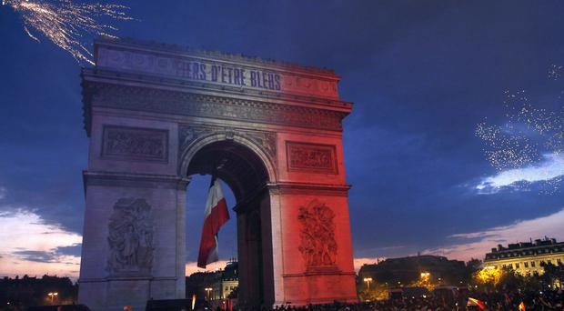 The Arc de Triomphe is illuminated with the colours of the French national flag (AP)