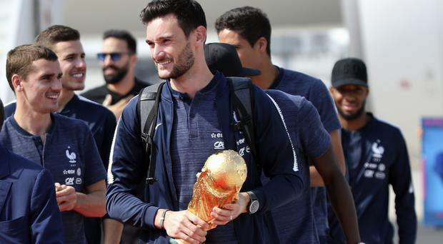 French goalkeeper and captain Hugo Lloris arrives clutching the World Cup (AP)