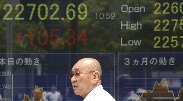 A man walks by an electronic stock board of a securities firm in Tokyo (AP)