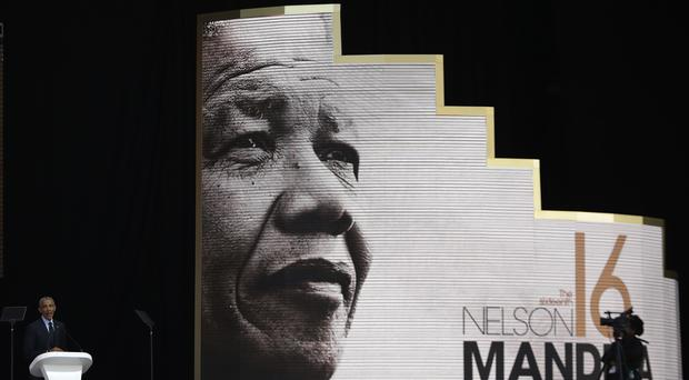 Former US president Barack Obama, left, delivers his speech at the 16th Annual Nelson Mandela Lecture (Themba Hadebe/AP)