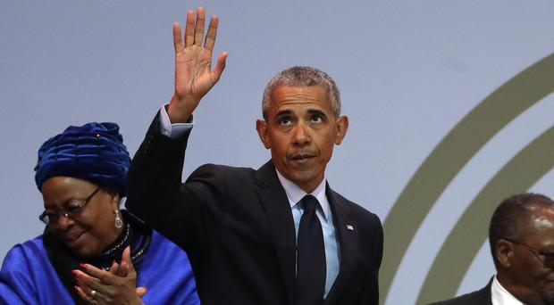 Former U.S. President Barack Obama, waves as he leaves the stage (Themba Hadebe/AP)