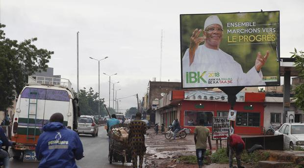 """Motorbike taxis ride past a giant poster of Mali's incumbent president Ibrahim Boubacar Keita that reads """"the great Mali advance"""" in Bamako (Baba Ahmed/AP)"""