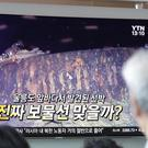 People at Seoul's railway station watch a TV screen showing a news programme reporting about a sunken Russian warship (Lee Jin-man/AP)