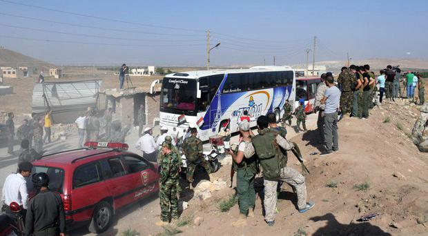 Syrian troops, journalists and civilians watch as buses evacuate people from the two pro-government villages of Foua and Kfarya, at Tel el-Eis, the crossing between Aleppo and Idlib provinces, Syria (Sana via AP)