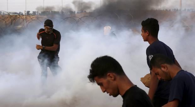 Protesters run for cover from tear gas fired by Israeli troops (Adel Hana/AP)