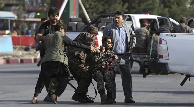 Afghan security personnel carry an injured comrade after the attack (Rahmat Gul/AP)