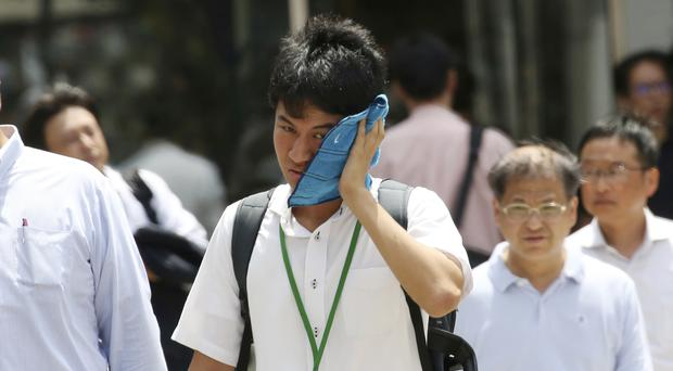 A man wipes the sweat from his face in the scorching heat at a business district in Tokyo (AP)