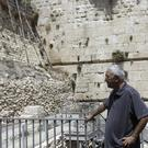 People stand near the part of the Western Wall where one of the stones dislodged (AP)