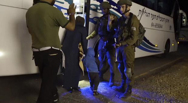 A member of the White Helmets waving to Israeli soldiers as he and his family board a bus (Israeli Defence Forces/AP)