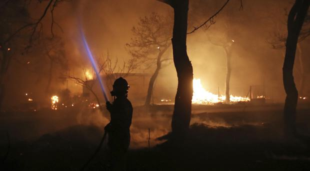A firefighter sprays water on the fire in the town of Mati, east of Athen (AP/Thanassis Stavrakis)