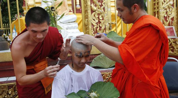 Soccer team member Pipat Pho's head is shaved (AP)