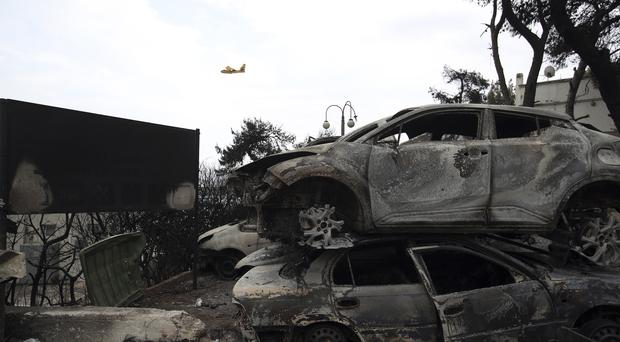 A firefighting plane flies above burned-out cars in Mati (AP)