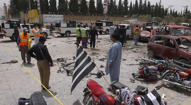 Pakistani volunteers and security officers visit the site of a bombing in Quetta (AP)