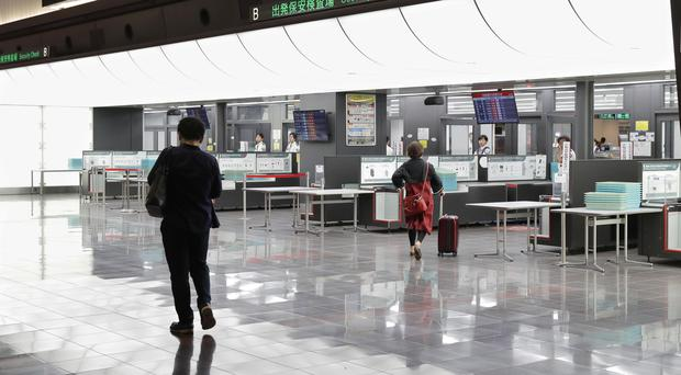 Two people walk in front of security check counters at a quiet Haneda international airport in Tokyo following the cancellation of flights (Kyodo News/AP)