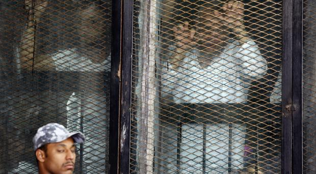 Some of the 739 defendants listen to the verdict from a soundproof glass cage inside a makeshift courtroom in Tora prison in Cairo, Egypt (Amr Nabil.AP)