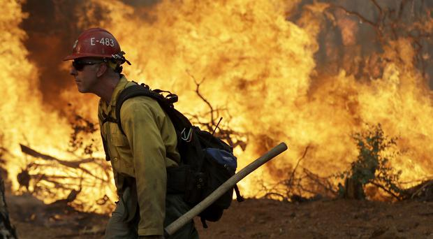 A firefighter walks along a containment line in front of an advancing wildfire in Redding, California (Marcio Jose Sanchez/AP)