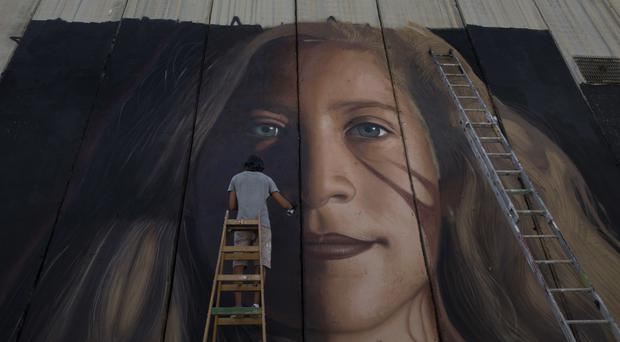 A giant mural of prominent Palestinian activist Ahed Tamimi on part of the Israeli separation wall, in the West Bank city of Bethlehem (AP)