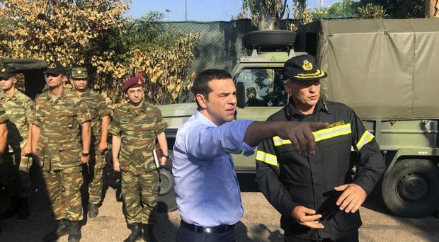 Greece's Prime Minister Alexis Tsipras talks with emergency services (AP)