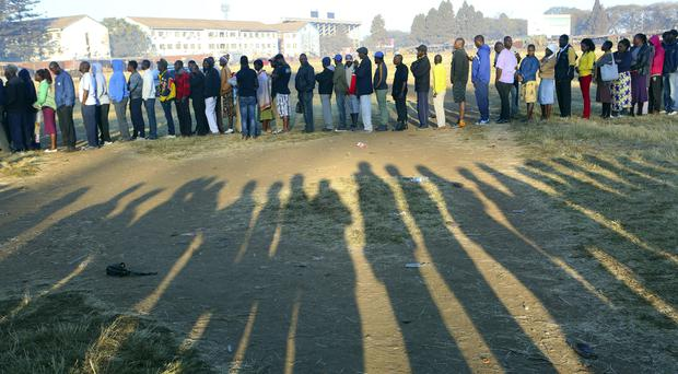 People wait in a queue to cast their vote at a polling station in Harare (AP)
