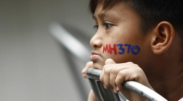 A Malaysian child at a remembrance ceremony for the missing flight MH370 (AP)