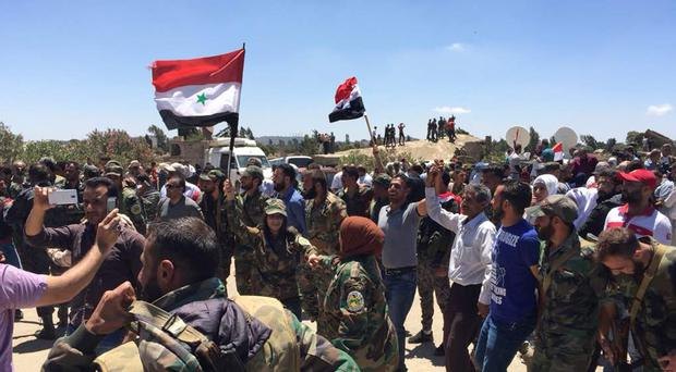 Syrian fighters and civilians celebrate the return of government authority to the southern town of Quneitra adjacent to the Israeli-occupied Golan Heights (AP)