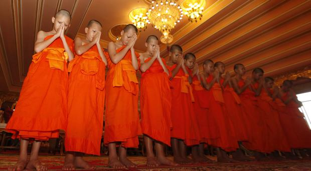 Members of the Thai football team rescued after almost three weeks in a cave pray during a ceremony marking the completion of serving as novice Buddhist monks (Sakchai Lalit/AP)