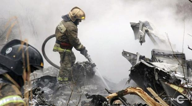A firefighter works at the site of a Russian helicopter crash (Russian government/AP)
