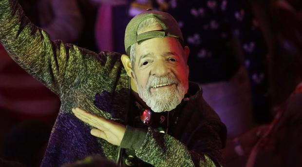 A man wears a mask depicting the Brazil's former president Luiz Inacio Lula da Silva during a Workers' Party national convention in Sao Paulo (AP)