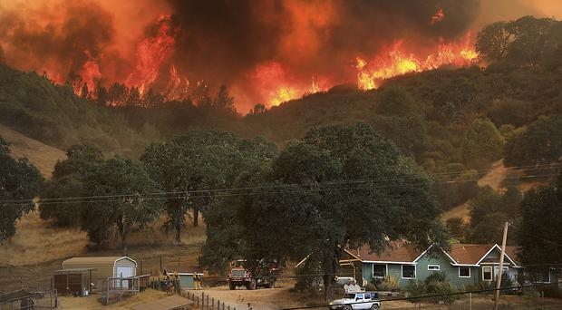 Flames from a wildfire advance down a hillside, towering over homes near Lakeport, California (Kent Porter /The Press Democrat via AP)