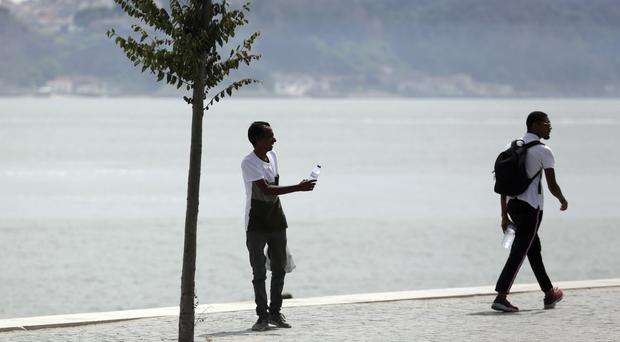 A man sells water bottles by a river in Lisbon (Armando Franca/AP)