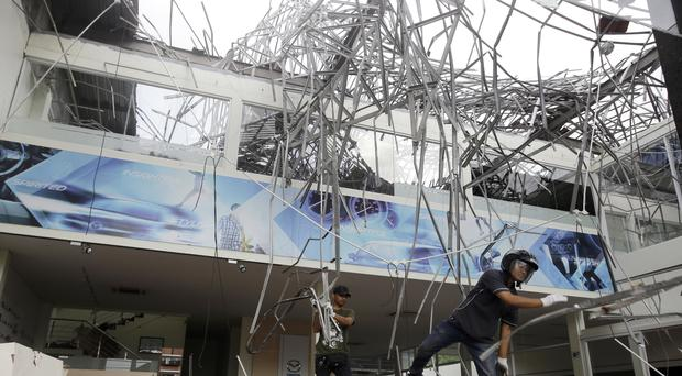 Workers remove the debris at a building damaged by an earthquake in Bali, Indonesia (Firdia Lisnwati/AP)