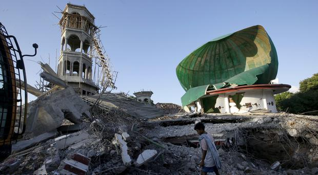 A resident inspects a mosque damaged by an earthquake in North Lombok, Indonesia (Tatan Syuflana/AP)
