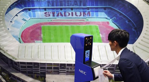 A staff member demonstrates a new face recognition system used for the Tokyo 2020 Olympic and Paralympic Games (Eugene Hoshiko/AP)