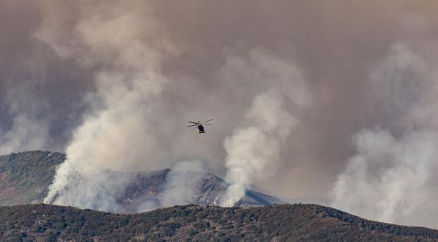 A water dropping helicopter heads towards the fire in Trabuco Canyon, California (Leonard Ortiz/The Orange County Register via AP)