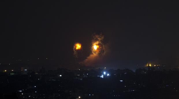 Fireballs caused by Israeli airstrikes on Gaza City (Khalil Hamra/AP)