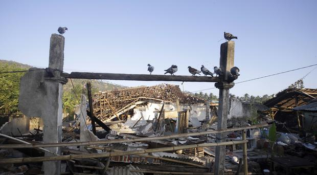 Birds sit above earthquake-damaged homes in North Lombok (AP)