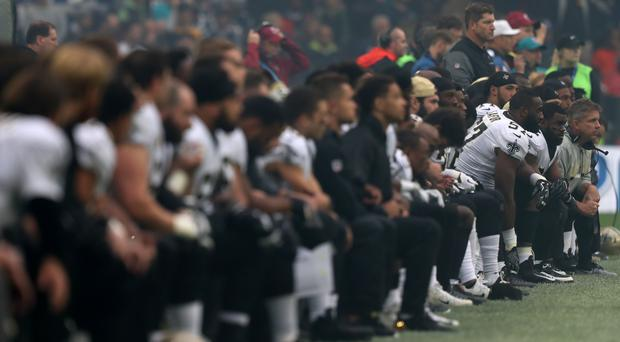 NFL players 'take a knee' during the US national anthem (Simon Cooper/PA)